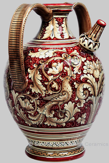 Italian majolica pitcher with twin handles and botanical decorations and bird motif