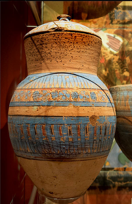 Egyptian blue painted terracotta jar decorated with geometric styled flowers and grapes, and a jar lid.
