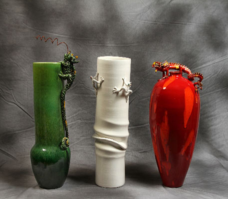 A green vase, red vase and white vase with lizrd figurinesby Mirta Morigi
