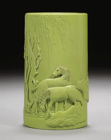 Avocado green cylindrical vase with sculptured horses along the bottom edge