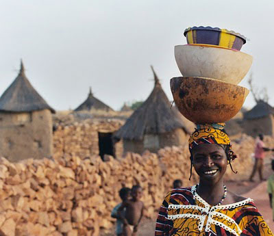 A Mali woman carryng pots in the village of Songha hjfklein - flickr