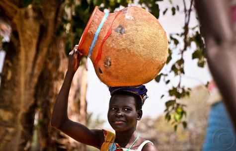 African girl carrying a pot