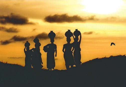 Women with pots at sunset in Sri lanka