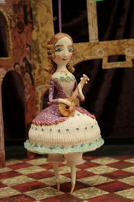 Young-girl-in-purple-dress-playing-mandolin.-Ceramic-bell,-sculpture.