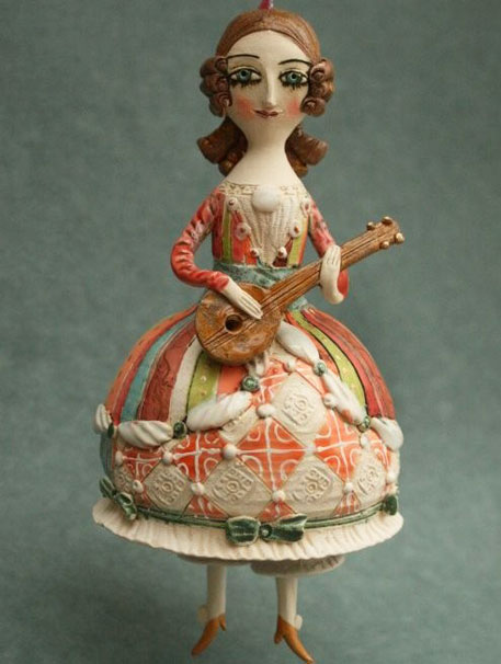 Young-girl-playing-mandolin.-Ceramic-bell,-sculpture.