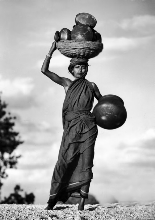 Indian woman carrying several pots in black and white vintage photo by Paul Joyce