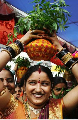 A women holding a pot in India decorated with neem leaves