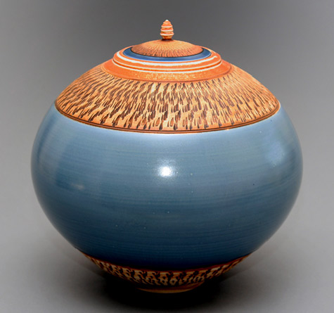 teal colour vessel with orange lid