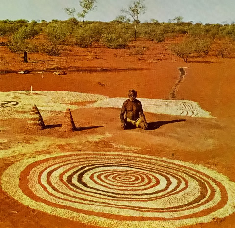 Australian aboriginal with sacred concentric circles motif on the red earth