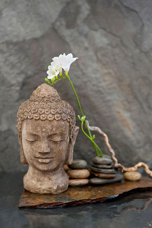 Elena-Ray---flickr buddha stone head with stones and a flower