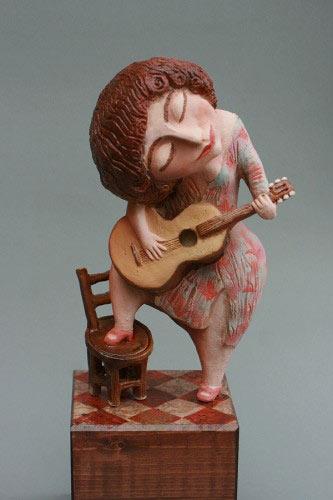 Elya Yalonetskaya - figurine of a red headed woman playing a guitar