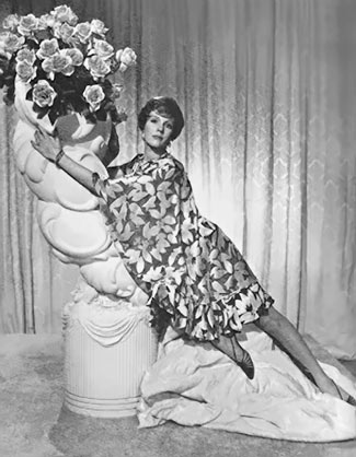 Julie Andrews posing on a large white ceramic vase