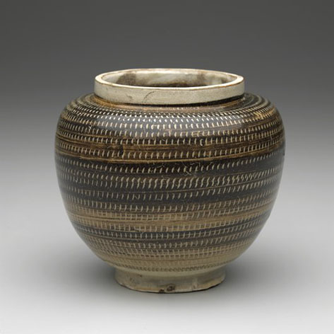 this jar is ornamented in the scraffito manner with an olive-brown overslip carved through to a white slip
