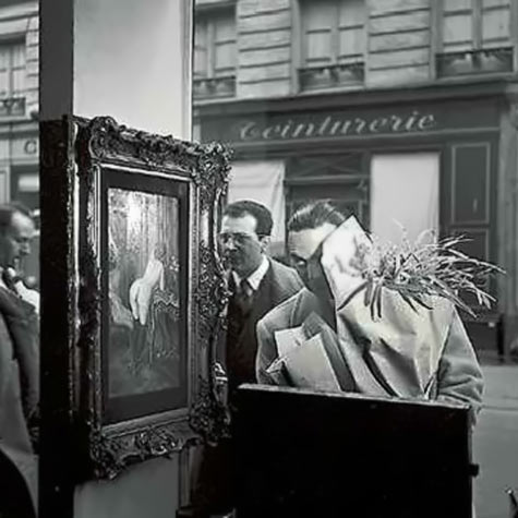 Doisneau a man sneaks a peek at a nude painting in a shop window