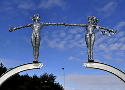 The Bridge - Andy Scott - a sculpture featuring two girls holding outstretched hands on an arch