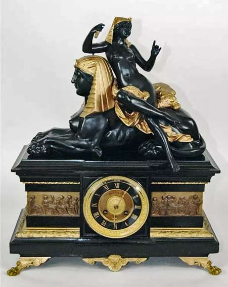 Egyptian-Revival-black-marble-and-bronze-case-clock-with-surrounding-Roman-relief-on-animal-paw-feet,-Egyptian-figure-of-nude-woman-leaning-on-Sphinx