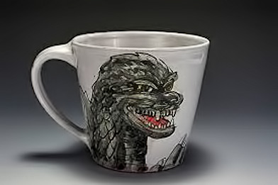 Godzilla-Mug-by-Eileen-de-Rosas - white ceramic mug with green godzilla motif