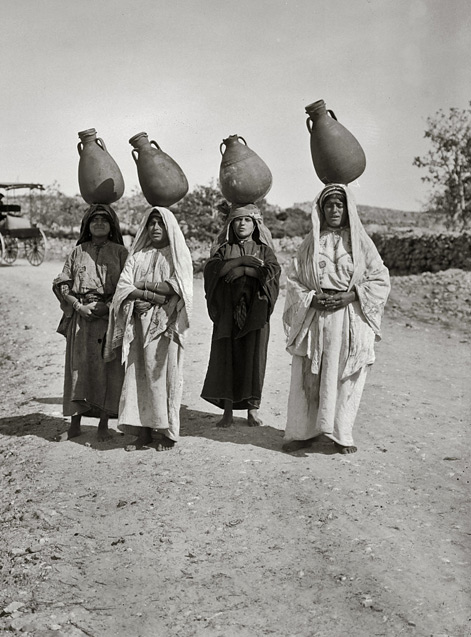 Four women carrying water jars,on their heads