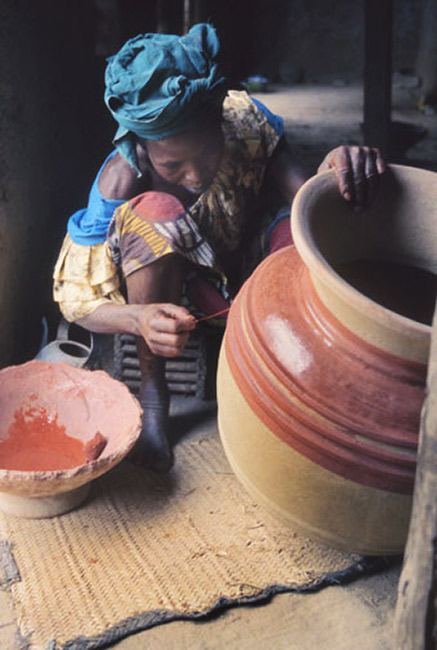 A red stone slip,-from an at market, is applied to the formed and dried pot before firing