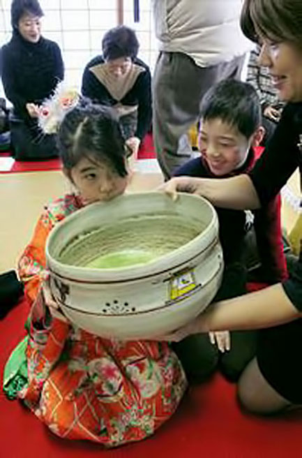 Young girl drinking from a Ochamori-'Big-Tea'-at-Saidaiji-temple-in-Nara