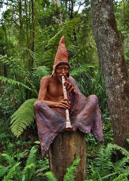 Sculpture-Garden-Bruno-Torfs - Bush forest minstrel sitting on a tree stump