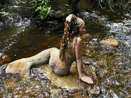 Mermaid sculpture in a mountain stream