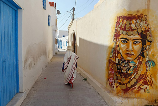 A-Tunisian-woman-walks-past-a-mural-by-Spanish-artist-Btoy.-Photograph--Mohamed-Messara-EPA