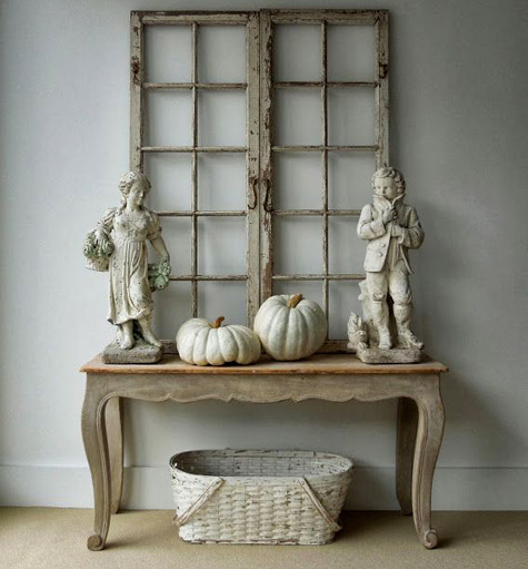 pair-of-18th-century-Swedish-windows,-garden-statues-depicting-the-seasons,-and-two-Lumina-pumpkins-on-a-French-painted-console.