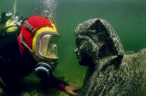 A-diver-eye-to-eye-with-a-sphinx-made-out-of-black-granite.-The-face-of-the-sphinx-is-believed-to-represent-Ptolemy-XII,-father-of-the-famous-Cleopatra-VII.