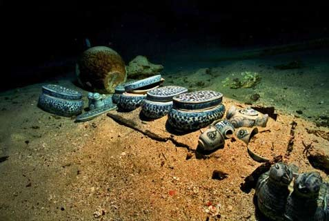 Porcelain dishes in blue and white appear after the sediment has been removed from the wreck of the Lena Shoal junk.