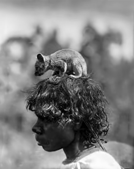A-Ponga-Ponga-woman-carries-a-pet-possum,-Northern-Territory,--1922
