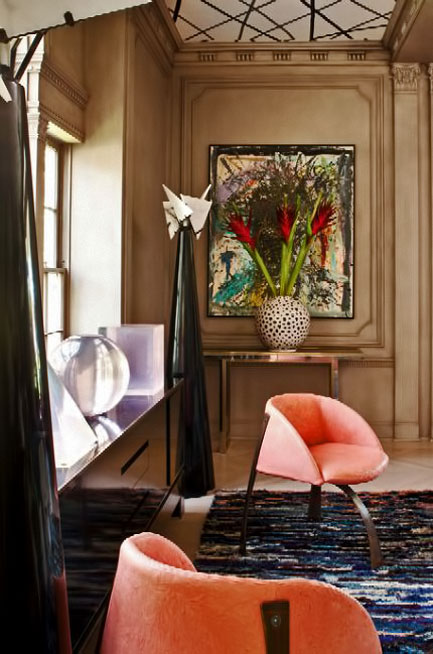 Loft-Concept-Kelly-Wearstler interior with large a pair of black conical sculptures, and white spherical vase with salmon pink chairs