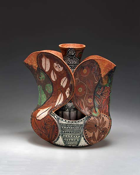 andrea-gill-meadows-gallery ceramic vessel encasing a vase with black and white geometric patterns