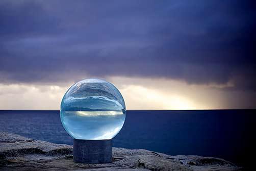 lucy-humphrey-horizon-sculpture-by-the-sea-bondi-2013 large glass sphere on the seaside rocks