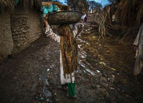 a girl carrying a bowl on her head in-the-slums-of-islamabad