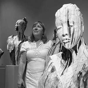 ann-goodfellow posing with her sculptures