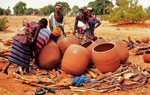 Arranging large Bamana pots for firing - Mali