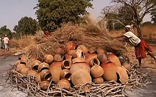 preparing a stack of pottery for firing in Mali