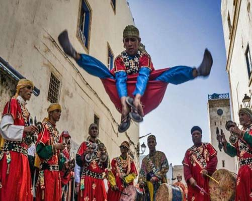 Gnawa musicians and leaping dancer