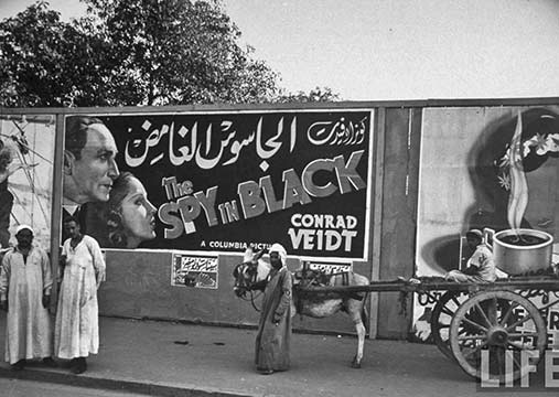 The Spy In Black movie poster in Ismalia in Egypt and a man with a dinkey and cart - photo - Margaret-Bourke-White