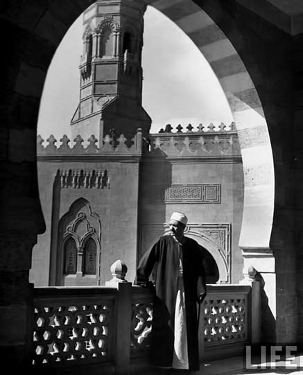 Faces-of-Egypt,-life-magazine,-circa-1940's An Egyptian man standing under a large arch