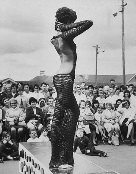 Fashion model Donyale Luna arching back while modeling backless see-through crocheted floor-length dress
