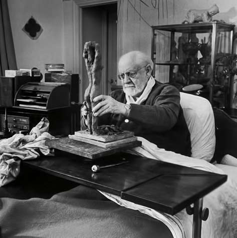 Henri Matisse sculpting nude female figure while sitting in bed in his apartment -Photographer-Dmitri Kessel
