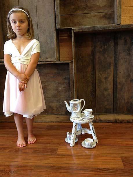 A girl with a tiny play teaset