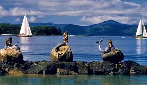 Three Daydream-Island-mermaid-sculptures on the waters edge by David Joffe