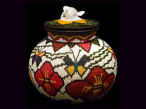Wounaan handwoven basket features a carved tagua nut hummingbird hovering and feeding on its lid