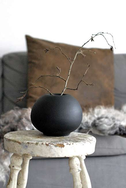 black ceramic globular vessel on white stool