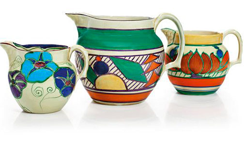 Three-clarice-cliff-jugs in the 'Fantasque' 'Fruit', 'Fantasque' 'Lily' and a 'Bizarre' pattern, the first 1928.