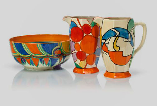 two-clarice-cliff-pitchers-and-a-centerpiece-bowlThe-pitchers-in-the-'Bizarre'-'Zap'-and-'Berries'-patterns,-athens-shape,-the-bowl-'Kandine'-pattern,-