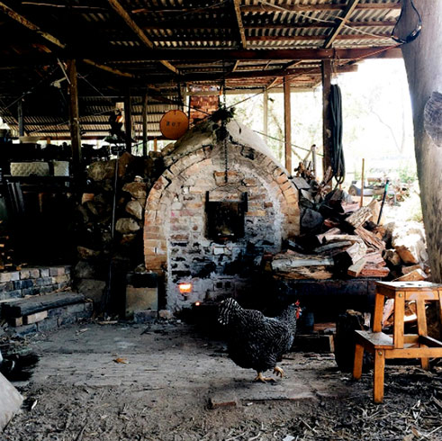 Audrey-the-wood-fire-kiln in the shed with a black chook